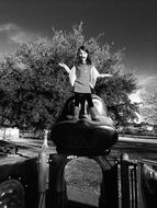 black white photo of a girl on the playground in the street