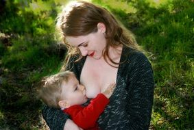 caucasion mom breastfeeding baby outdoor