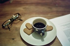glasses, a cup of coffe with heart cookies and a book on a wooden table