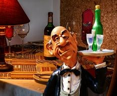 statue of an old waiter with a tray with glasses and wine