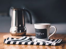 coffee pot with a mug on a striped cloth napkin