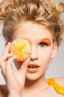 model with orange makeup holding peeled orange