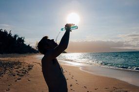 man drinking water on the beach