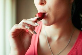 sexual woman biting strawberry