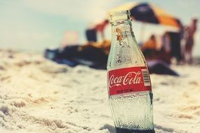 coca cola bottle in a sand