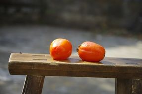 Two fruits lie on a bench