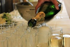 hand pouring champagne in glasses