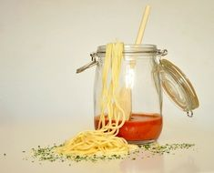 spaghetti noodles and tomato sauce in a glass jar