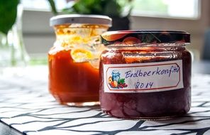 Cooked jam with berries in glass jars