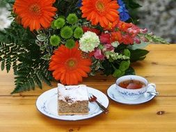tea , cake and bouquet of flowers