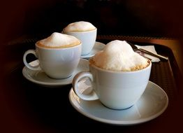 three cups of cappuccino on a tray