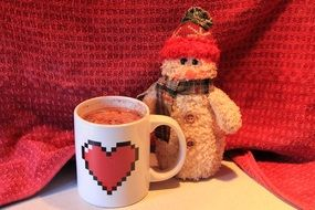hot chocolate in cup andsnowman toy, christmas still life