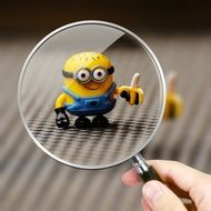 funny minion toy through magnifying glass
