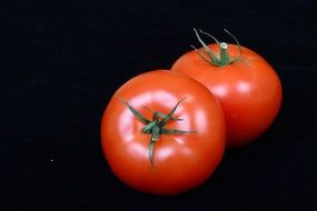 two red ripe tomatoes on a black background