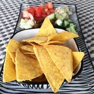 nachos with diced vegetables in a plate