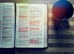 bible on the table next to a cup of coffee