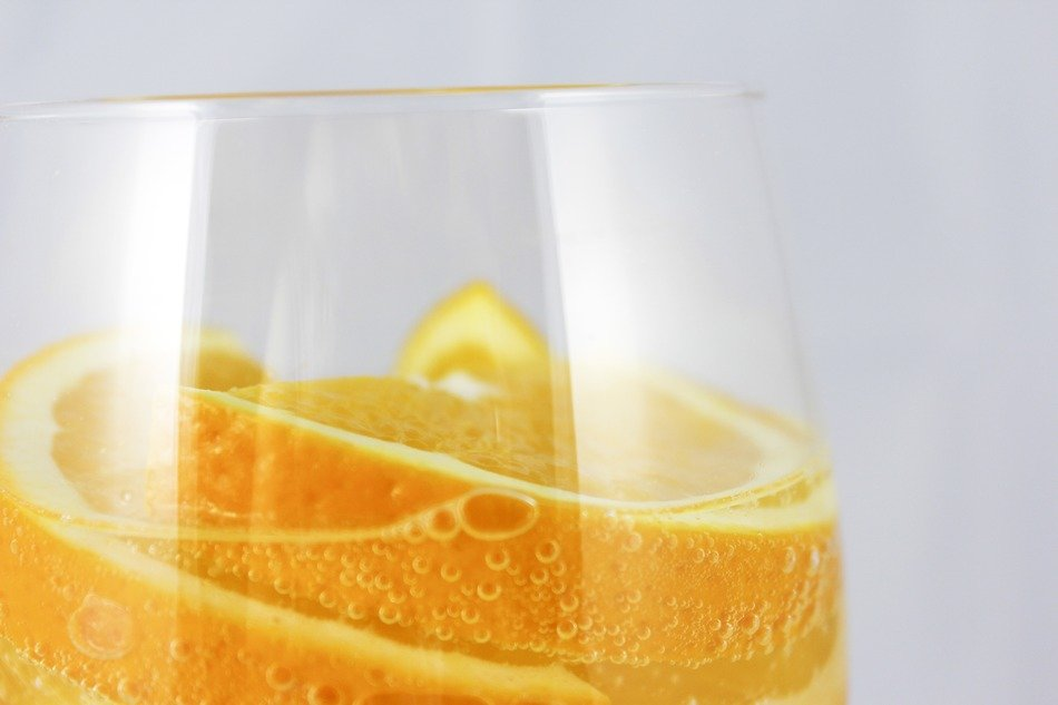 sliced oranges in glass with water