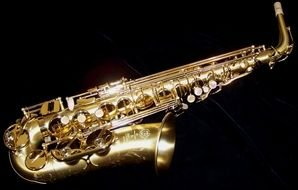 photo of golden shiny saxophone on black background