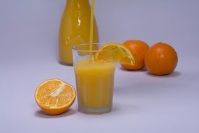 orange juice in glass with slice of orange