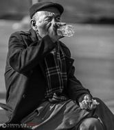black white old man drinking water