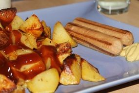 fried potatoes with ketchup and sausages
