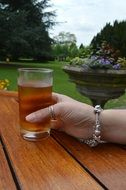 drink glass in hand with braslet and ring