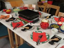 table served for raclette cheese party, nobody
