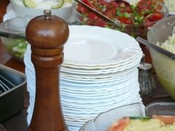 pepper mill and many white plates