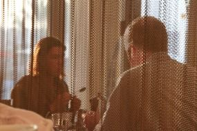 couple in a cafe behind the curtain