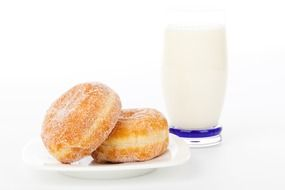 a glass of milk and two donuts