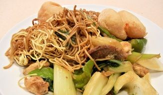 chinese noodles with other ingredients on a white plate