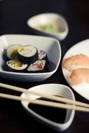 sushi and soy sauce in white ceramic bowls