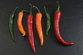 chili peppers of different colors on a dark surface