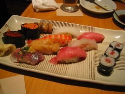 raw sushi and rolls on dish