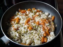 rice with vegetables is fried in a pan