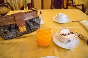 louis vuitton bag, cappuccino cup and fruit drink on the table