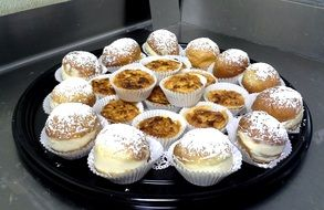 delicious cupcakes with powdered sugar on a tray