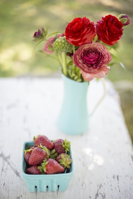 rose bouquet and strawberries in box on table