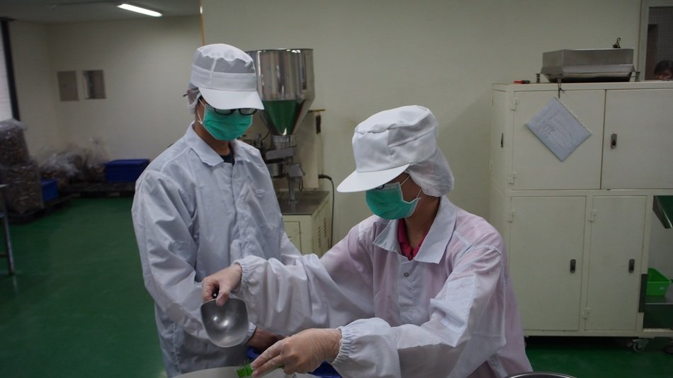 workers in white coats at a food factory