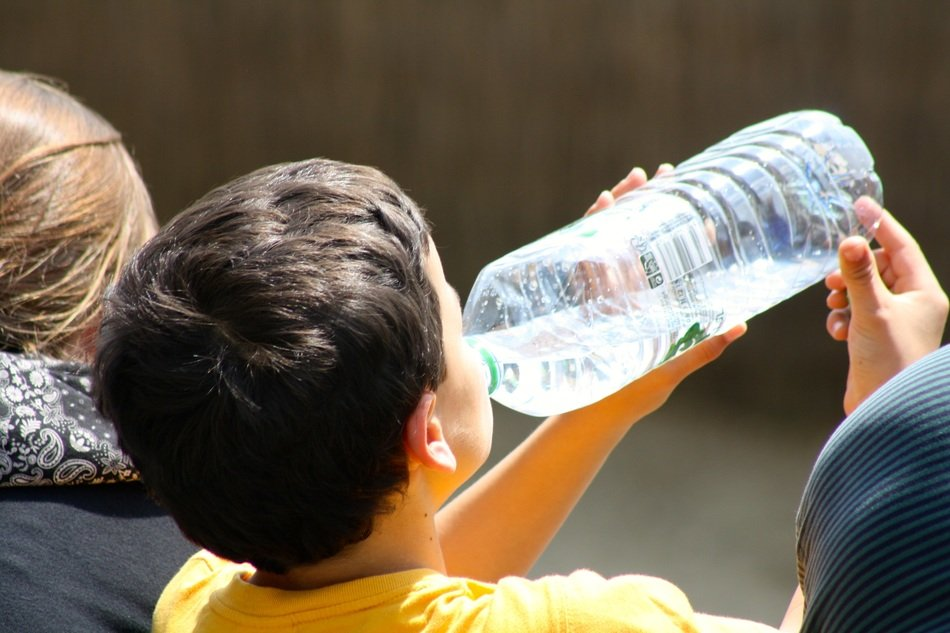 boy drinks water from a bottle on a sunny day