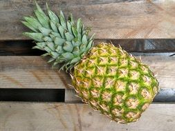 pineapple fruit on wooden plank