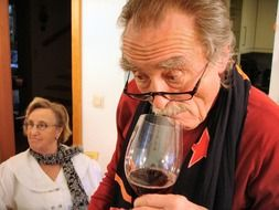 elderly man with a glass of red wine