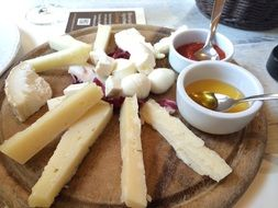 Parmezan and mozzarella cheeses on the wooden plate