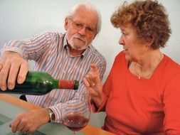 elderly couple is drinking red wine