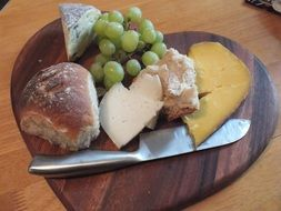bread, cheese and grapes on a wooden board