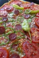 Italian pizza with salami and vegetables