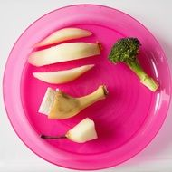 half a banana, half an apple, half pear and broccoli on a plate