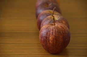 row of red apples on brown surface