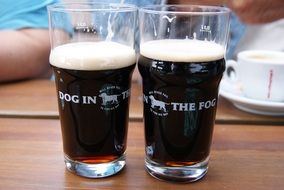 two glasses of dark beer
