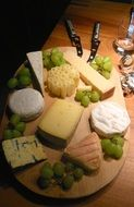 cheeses of different types on a wooden board
